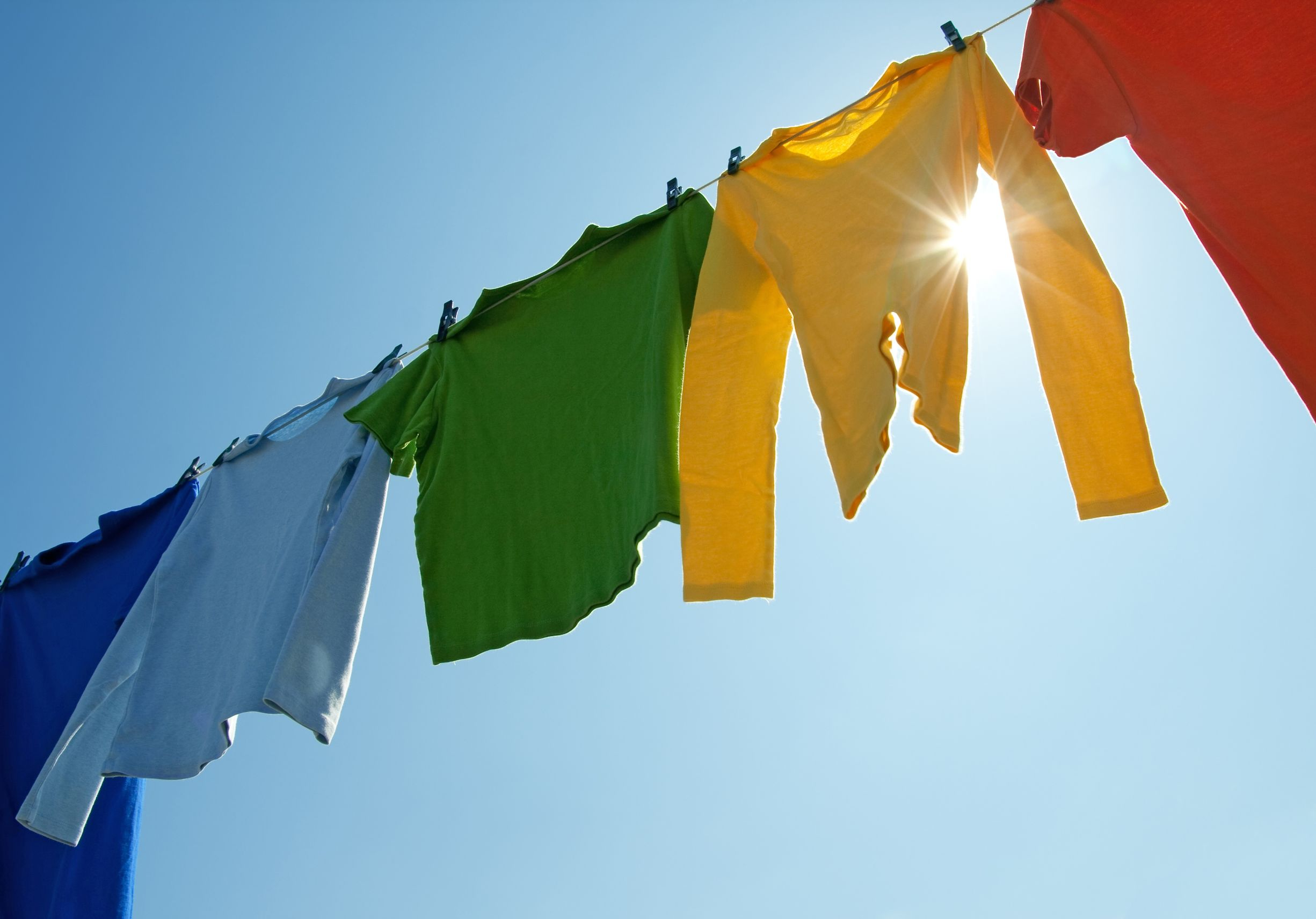 10856478 - colorful clothes hanging to dry on a laundry line and sun shining in the blue sky.